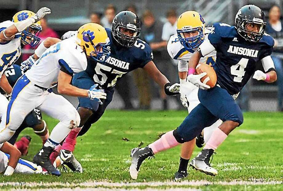 Ansonia's Malcolm Martin (57) punches open a hole for Tajik Bagley vs Seymour last year. Both players return in 2015. Photo: Peter Hvizdak -- New Haven Register