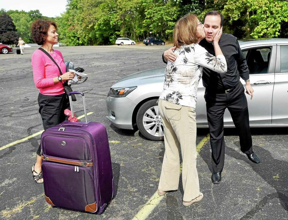 (Arnold Gold-New Haven Register)  Noreen Wolleben of Guilford kisses Father Andres Mendoza of New Britain goodbye as she prepares to board a bus in the parking lot of Our Lady of Pompeii Church in East Haven for a trip to Philadelphia and the World Meeting of Families on 9/25/2015.  At left is Diane Birdsall of Madison. Photo: Journal Register Co.
