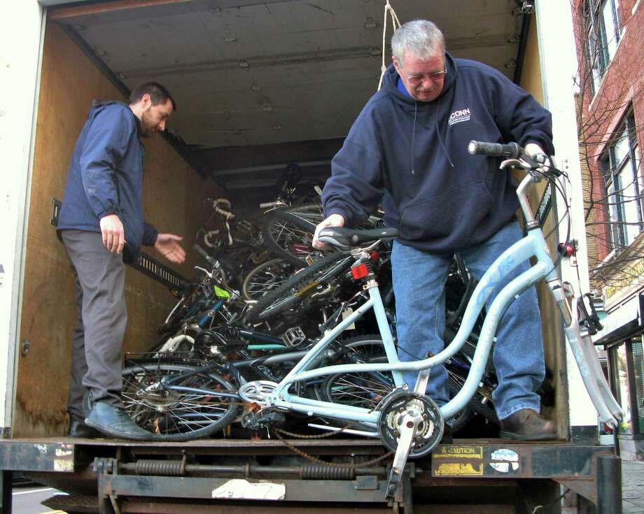 Nathan Bedard, left, and Ron Ethridge with the UConn facilities department, unload bicycles Dec. 10 at the Center for Latino Progress in Hartford, Conn. The school says about 100 bikes a year are abandoned on campus. They are being donated to the center, which runs a program that allows people to repair one bike for a donation to a shelter and another to keep.  (AP Photo/Pat Eaton-Robb) Photo: Associated Press   / A