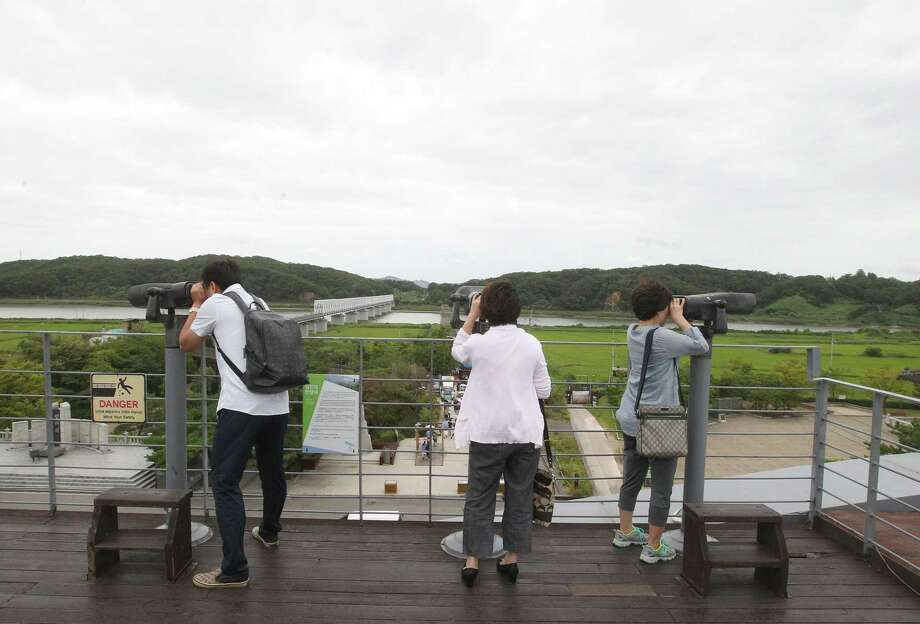 Visitors use binoculars to watch north side at the Imjingak Pavilion near the border village of Panmunjom, which has separated the two Koreas since the Korean War, in Paju, South Korea, Tuesday, Aug. 25, 2015. After more than 40 hours of talks, North and South Korea pulled back from the brink Tuesday with an accord that allows both sides to save face and, for the moment, avert the bloodshed they've been threatening for weeks. Photo: AP Photo/Ahn Young-joon / AP
