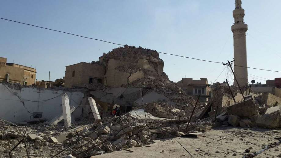 In this July 27, 2014, file photo, people inspect the destroyed old Mosque of The Prophet Jirjis in central Mosul, Iraq. The revered Muslim shrine was destroyed by militants who overran the city in June and imposed their harsh interpretation of Islamic law. The rampage by IS, targeting priceless cultural artifacts often spanning thousands of years, has sparked global outrage and accusations of war crimes. Photo: AP File Photo   / AP