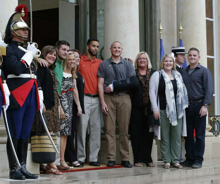 Anthony Sadler, center with orange shirt, a senior at Sacramento State University in California, U.S. Airman Spencer Stone, fourth from right, U.S. National Guardsman from Roseburg, Ore., Alek Skarlatos, third from left, and their families pose with U.S. Ambassador to France Jane D. Hartley, fourth from left, on the steps of the Elysee Palace before being awarded with the Legion of Honor Monday in Paris, France. Photo: AP Photo   / AP