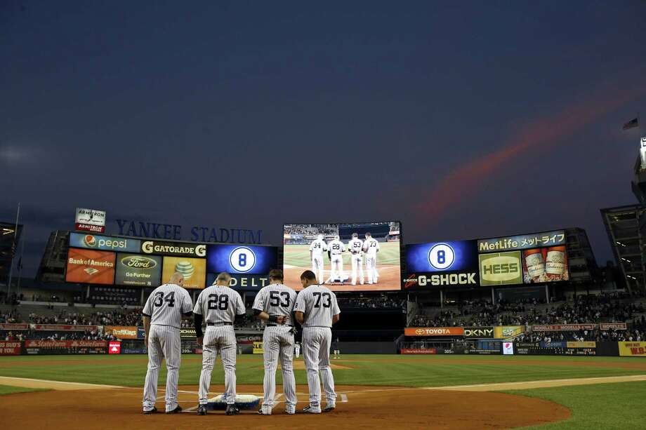 Yankees manager Joe Girardi places flowers on home plate in remembrance of Yogi Berra prior to Thursday's  game against the White Sox. Photo: Adam Hunger — The Associated Press   / FR110666 AP