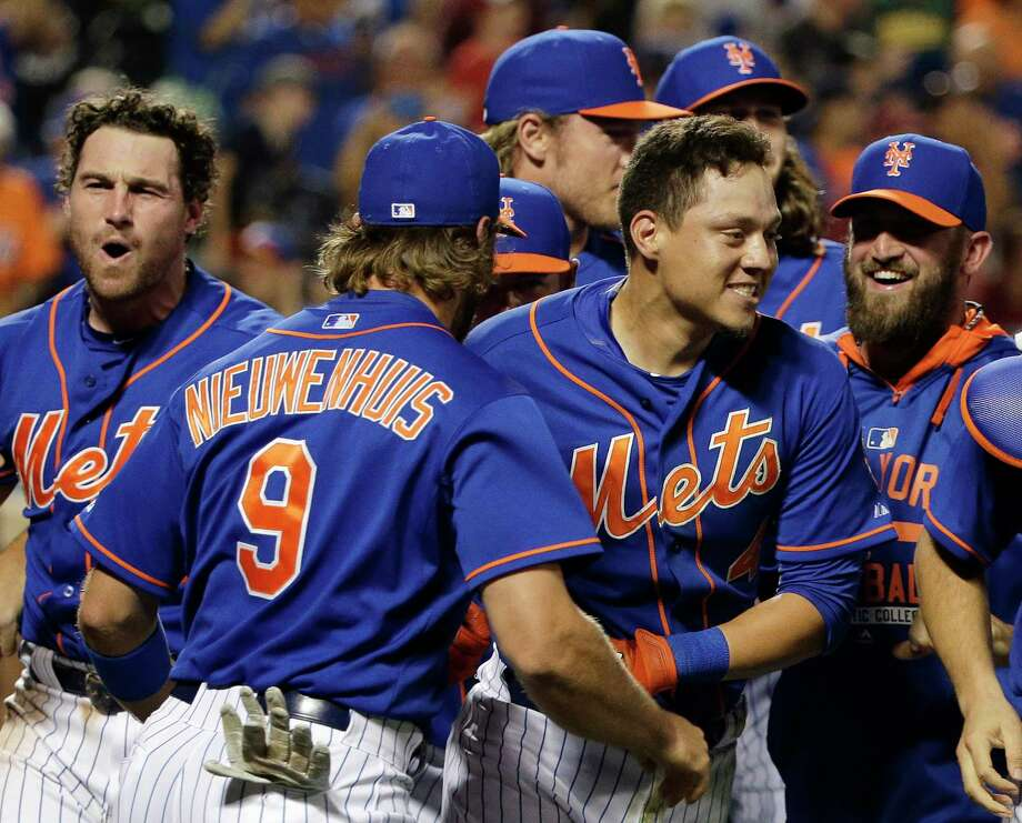 In this file photo from July 31, the Mets' Wilmer Flores, center right, is mobbed by teammates after hitting a walk-off solo home run during the 12th inning to beat the Nationals just two days after Flores thought he had been traded. Photo: The Associated Press File Photo   / AP