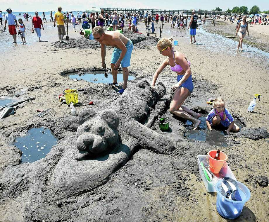 Left to right: Andy Sperazza of Stamford, his wife, Victoria, and daughter, Sophia, 5, work on a surfing teddy bear at the annual Walnut Beach Sand Sculpture Competition in Milford on 7/25/2015. Photo: (Arnold Gold-New Haven Register)
