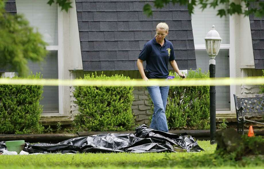 An investigator walks past a tarp covering a body in the front yard of a house in Broken Arrow, Okla., Thursday, July 23, 2015, where five family members were discovered stabbed to death. Police were questioning two teenage brothers in connection with the deaths of their parents and three younger siblings. A 2-year-old sister was found unharmed. Photo: (AP Photo/Sue Ogrocki) / AP
