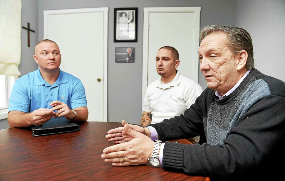 (Arnold Gold-New Haven Register) Left to right, Michael P. Hayes-Moore, assistant director, and Steve Stokes, program facilitator, listen to Pastor Rick Welch, executive director, being interviewed at Teen Challenge offices in New Haven on 11/19/2015.