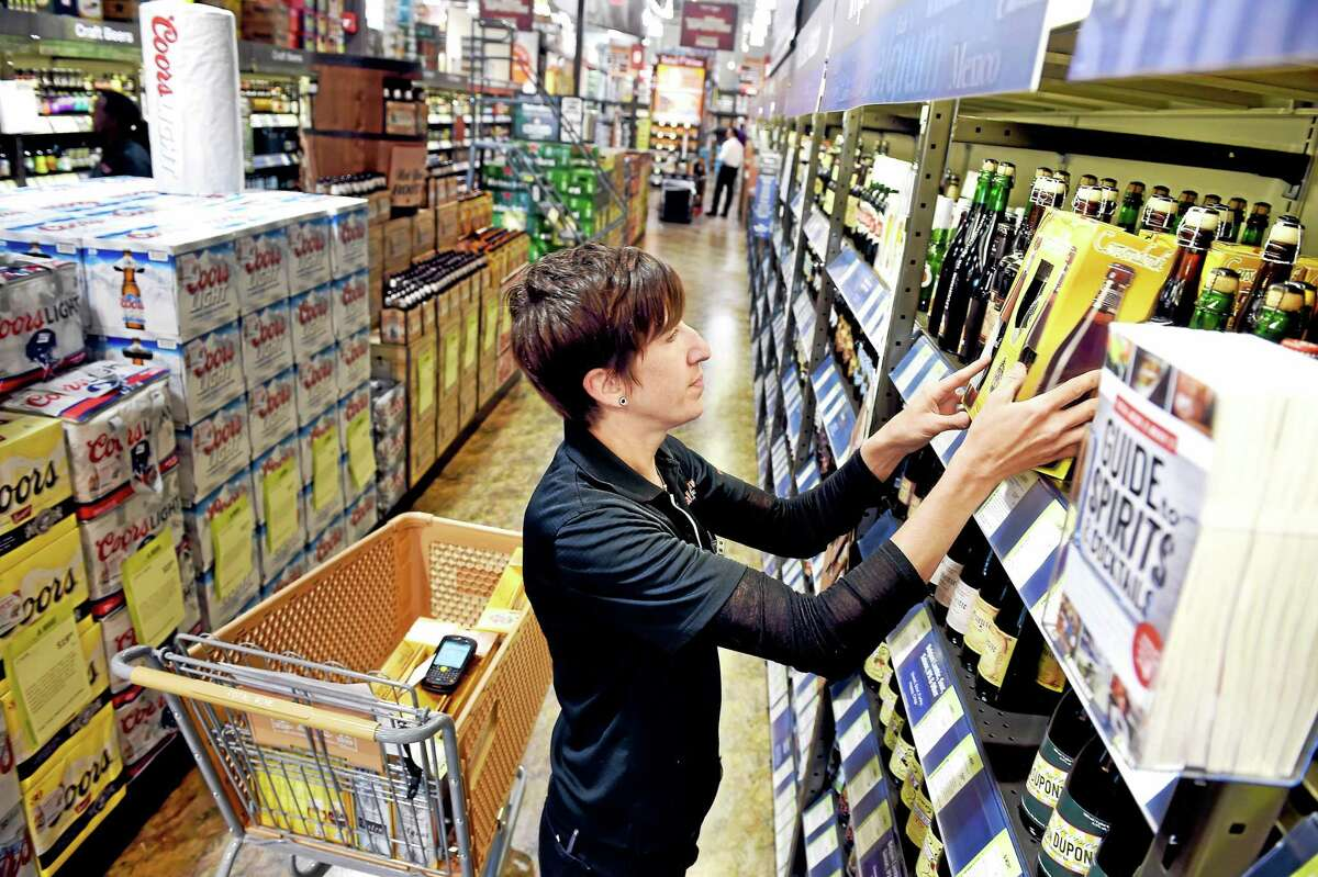 Beer Specialist Beth O'Callaghan stocks beer on shelves at Total Wine & More at 230 Cherry St. in Milford.