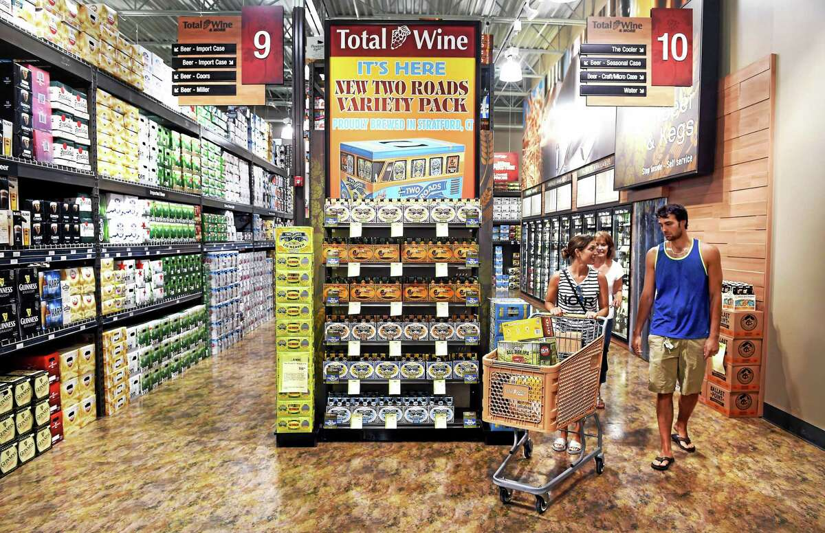 From left, Christine Noi of Trumbull, her mother, Darlene Coppola of Norwalk, and husband, Daniel Noi, shop in the beer section at Total Wine & More in Milford.
