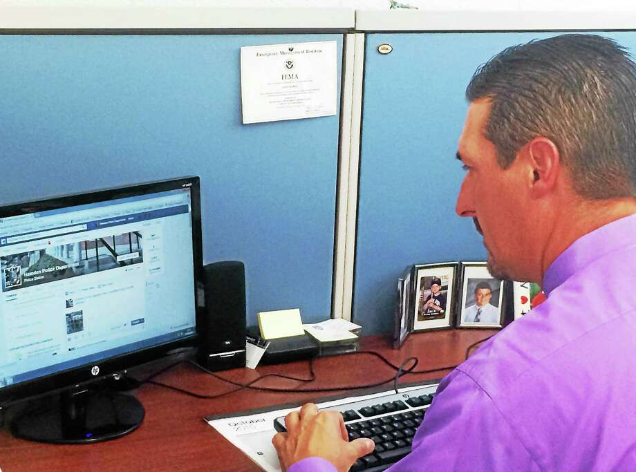 Hamden Detective John Marks adds a post to the department's Facebook page from his desk at police headquarters. Marks has worked to give the department a much more active social media presence over the past year. Photo: Wes Duplantier — New Haven Register
