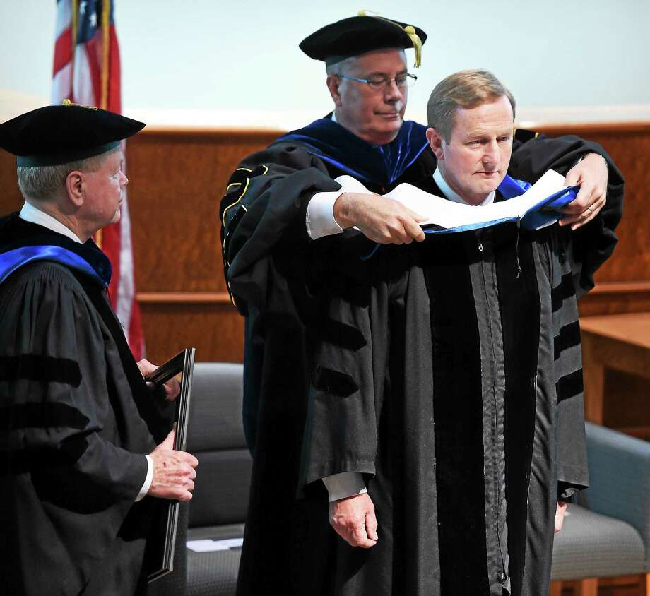 Enda Kenny, Taoiseach of Ireland, is hooded by Quinnipiac University Provost Mark Thompson during a ceremony in the university's Center for Communications and Engineering in Hamden Thursday.  At left is Quinnipiac University Trustee Hugh Keefe Photo: (Arnold Gold — New Haven Register)