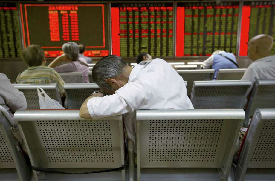 Chinese investors monitor stock prices at a brokerage house in Beijing, Tuesday, Aug. 25, 2015.  China's main stock market index has fallen for a fourth day, plunging 7.6 percent to an eight-month low. Photo: AP Photo/Mark Schiefelbein   / AP