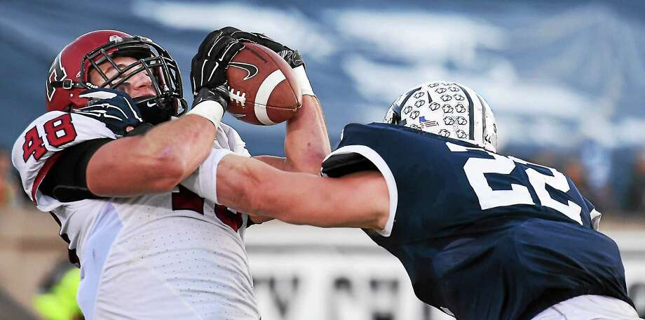 Harvard senior tight end Ben Braunecker catches a touchdown pass as Yale's Matthew Oplinger defends during Saturday's game at the Yale Bowl. Photo: Catherine Avalone — New Haven Register   / Catherine Avalone/New Haven Register