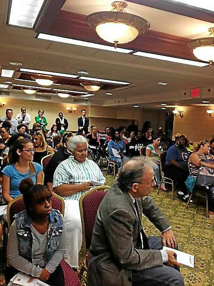 Around 90 adults and children listened Thursday at the Clarion Hotel in Hamden as officials explained the process to get some 45 families that moved out of Church Street South out of hotels and into apartments. Photo: (Mary O'Leary — New Haven Register)