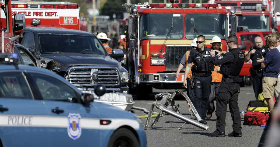 Emergency vehicles surround the site of a deadly crash between a charter bus and an amphibious tour vehicle in Seattle on Thursday, Sept. 24, 2015. Seattle fire officials say two people have been killed and numerous others critically injured in the crash that happened on a bridge over Lake Union. Photo: (AP Photo/Elaine Thompson) / AP