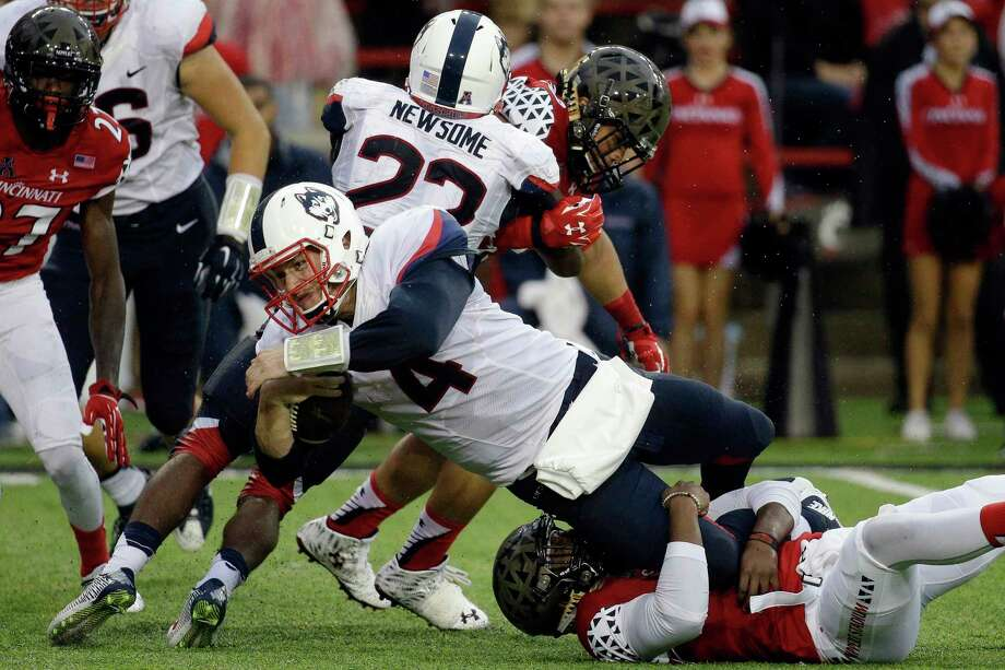 UConn quarterback Bryant Shirreffs (4) is tackled by Cincinnati safety Zach Edwards in the first half Saturday. Photo: John Minchillo — The Associated Press   / AP