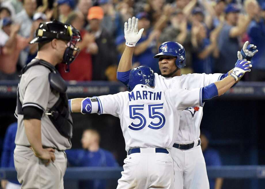 The Blue Jays' Russell Martin (55) celebrates with Edwin Encarnacion after Martin's three-run home run as New York Yankees catcher Brain McCann, left, looks on during the Blue Jays' 4-0 win. Photo: Nathan Denette/The Canadian Press Via AP    / The Canadian Press
