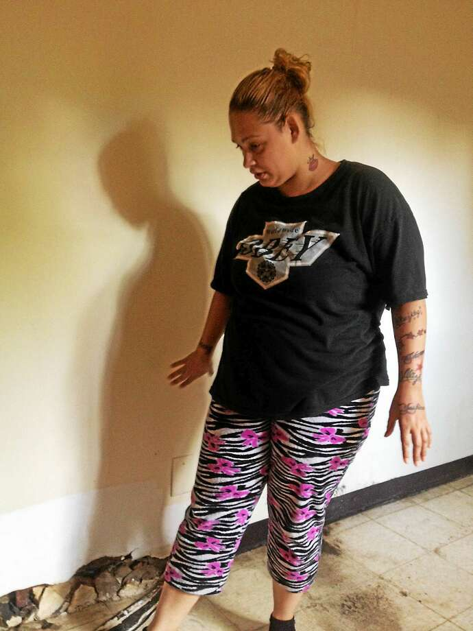 Tahis Caraballo looks at crumbling baseboard in room where water oozes from the floor tile in unusable bedroom. Photo: Mary O'Leary/New Haven Register