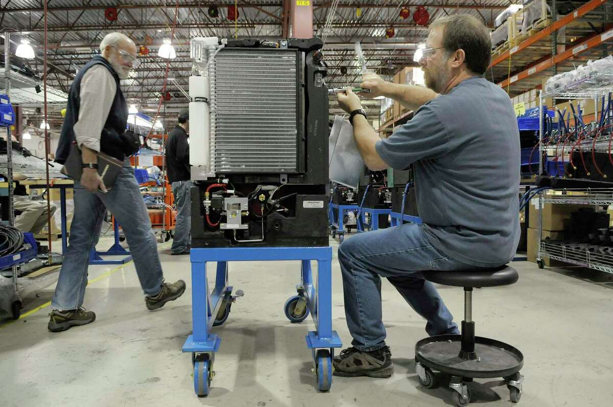 Jim D'Aleo, left, an engineer, and Paul Graney, right, a senior production technician, work on the Class 2 GenDrive at Plug Power on Wednesday, Nov. 10, 2010, in Latham, N.Y. (Paul Buckowski / Times Union)