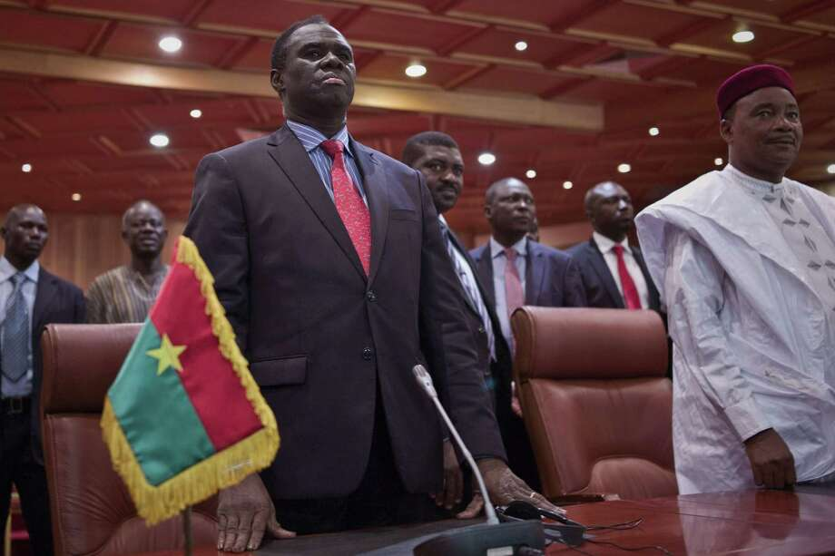 Burkina Faso's transitional president Michel Kafando, left, next to Niger's President, Mahamadou Issoufou, right, during a official handover ceremony  in Ouagadougou, Burkina Faso, Wednesday, Sept. 23, 2015. Amid cheers and the national anthem, Burkina Faso's interim president took charge of the country again Wednesday a week after a military general and his supporters overthrew him and his transitional government. Interim President Michel Kafando and Prime Minister Yacouba Isaac Zida marked their return to power in an official handover ceremony in Ouagadougou. Photo: AP Photo    / AP