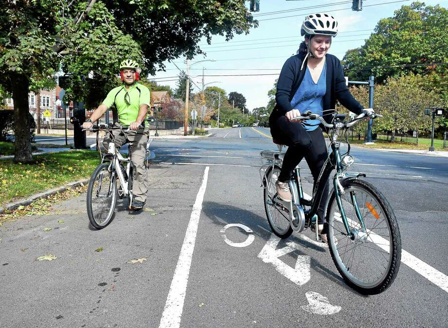 Martin Torresquintero, left, outdoor adventure coordinator for the New Haven Department of Parks, Recreation and Trees, watches New Haven Register reporter Anna Bisaro try out an electric assist bicycle on Yale Avenue in New Haven. Photo: Arnold Gold — New Haven Register