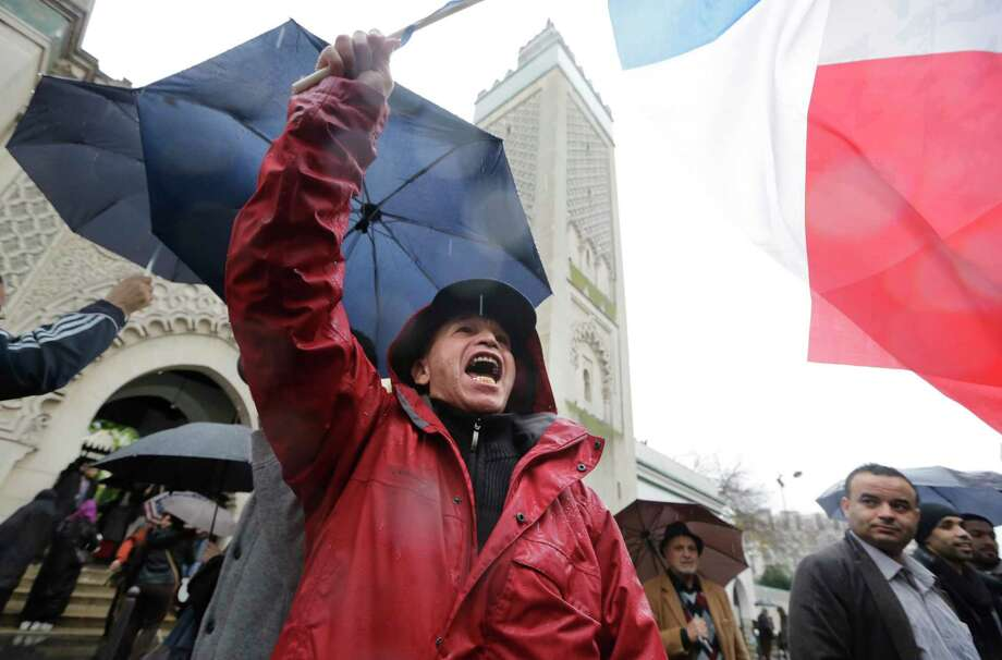 A man identified only as Sherif waves the French flag and shouts anti-radical islam slogans after Friday prayer at the Paris mosque Friday Nov.20, 2015. Cold rain extinguished the flickering candles and drenched the packets of flowers outside the Paris attack sites Friday, but people came anyway — to pay tribute, to mourn, to reflect on their city's losses one week later. Photo: AP Photo/Amr Nabil    / Amr Nabil