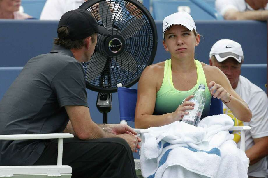Simona Halep listens to her coach Darron Cahill, left, during her match against Serena Williams at the Western & Southern Open on Sunday. Halep, the top seed for the Connecticut Open, withdrew from the tournament Sunday night. Photo: John Minchillo — The Associated Press   / AP
