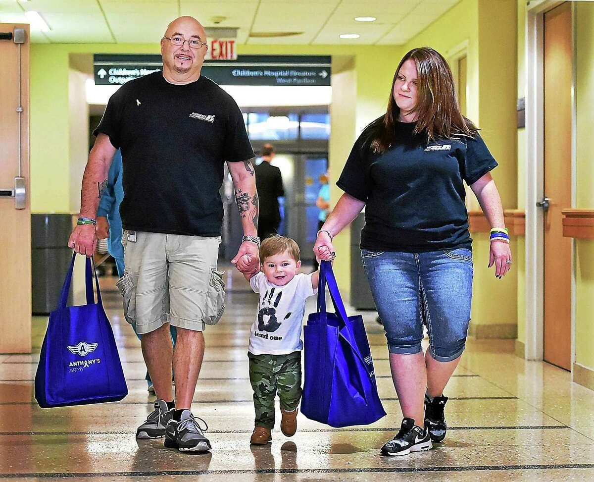 "Anthony Muoio, 17 months old, and his parents, Robert and Sarah Muoio, deliver ""bags of hope"" to Yale-New Haven Children's Hospital Wednesday."