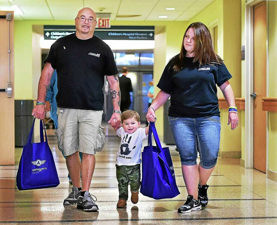 """Anthony Muoio, 17 months old, and his parents, Robert and Sarah Muoio, deliver """"bags of hope"""" to Yale-New Haven Children's Hospital Wednesday. Photo: Catherine Avalone — New Haven Register   / New Haven RegisterThe Middletown Press"""
