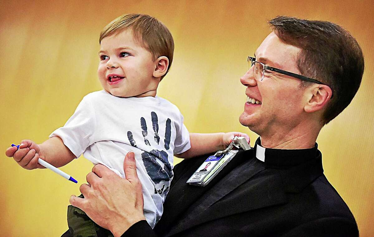 Anthony Muoio, 17 months old, visits with the Rev. Bill Maguire, chaplain in the Department of Spiritual Care at Yale-New Haven Children's Hospital, Wednesday. A year ago, Anthony endured a 9-hour surgery to remove a life-threatening brain tumor. Maguire offered spiritual guidance to Sarah and Robert Muoio, Anthony's parents.