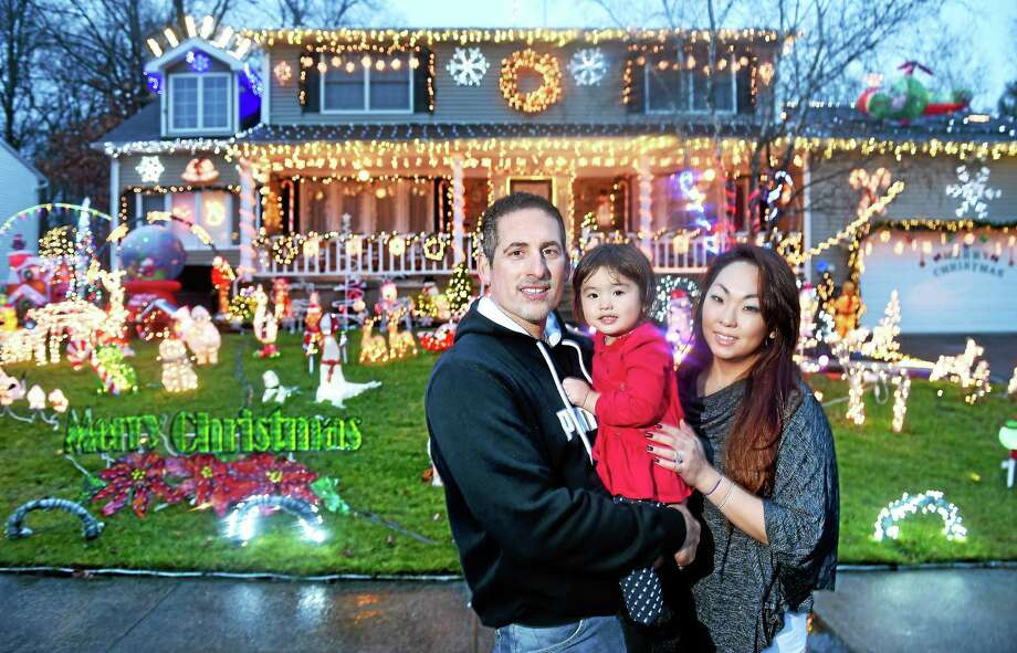 Ron Celentano (left) with his daughter, Isabella, 2, and wife, Crystal, are photographed in front of their home with an elaborate Christmas display in West Haven. Photo: Arnold Gold — New Haven Register