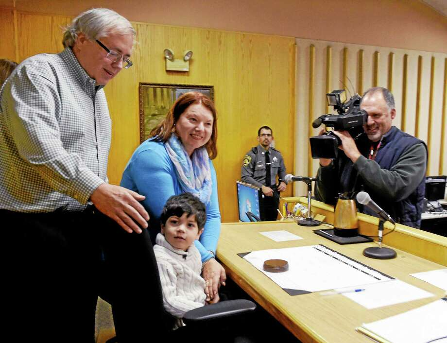 Donald and Joanne Grailich of Milford celebrate with their newly adopted son Joseph, 4, as he sits in the judge's chair at the New Haven Juvenile Court after his adoption Friday. At right is WTNH news photographer Kevin Phlaumer. Photo: Peter Hvizdak — New Haven Register   / ?2015 Peter Hvizdak