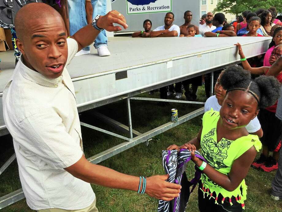 Esteban L. Hernandez New Haven Register   The Rev. Eldren D. Morrison, left, hands out a backpack to a young girl during the Varick Family Reunion Day on Sundayin New Haven. The backpacks were donated by members of Varick Memorial AME Zion Church in New Haven, were Morrison serves as pastor. Photo: Journal Register Co.