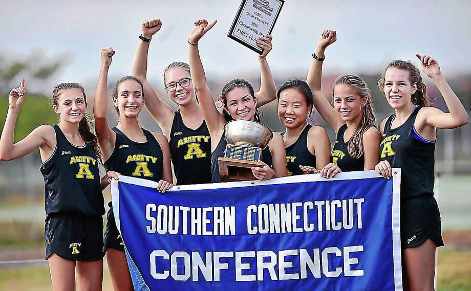 The Amity Spartans, the winners of the Southern Connecticut Conference girls cross country championship meet hold up their trophy and banner Thursday at Hammonasset Beach State Park in Madison. Photo: Catherine Avalone — New Haven Register    / New Haven RegisterThe Middletown Press