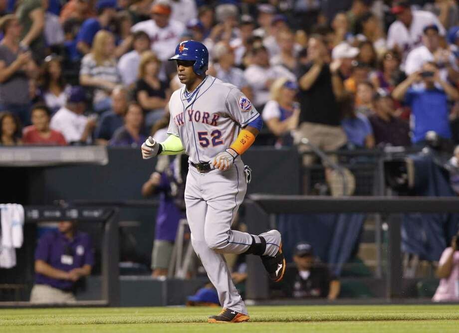 Fans stand and cheer as New York Mets' Yoenis Cespedes, front, circles the bases after hitting a solo home run off Colorado Rockies relief pitcher Christian Bergman to lead off the top of the fourth inning of a baseball game Friday, Aug. 21, 2015, in Denver. (AP Photo/David Zalubowski) Photo: AP / AP
