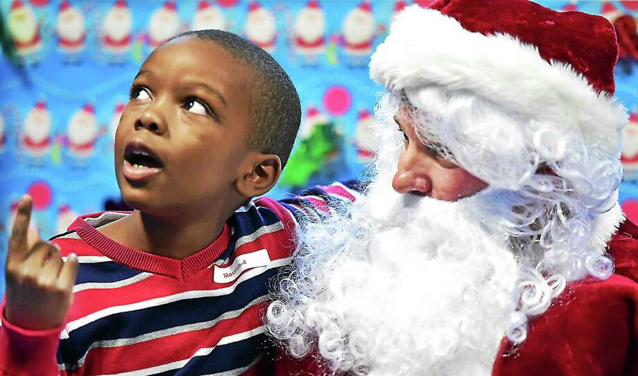 """(Catherine Avalone - New Haven Register)  Maurice Carrington, 7, of Hamden sits on the lap of a """"sensitive"""" Santa who meets with children on the autisim spectrum one on one in a low-stimuli setting at a holiday party, Saturday, December 19, 2015, at ASD Fitness at 307 Racebrook Road in Orange. Carrington said, """"Santa said I'm a very good boy. I love it here."""" Photo: Journal Register Co. / New Haven RegisterThe Middletown Press"""