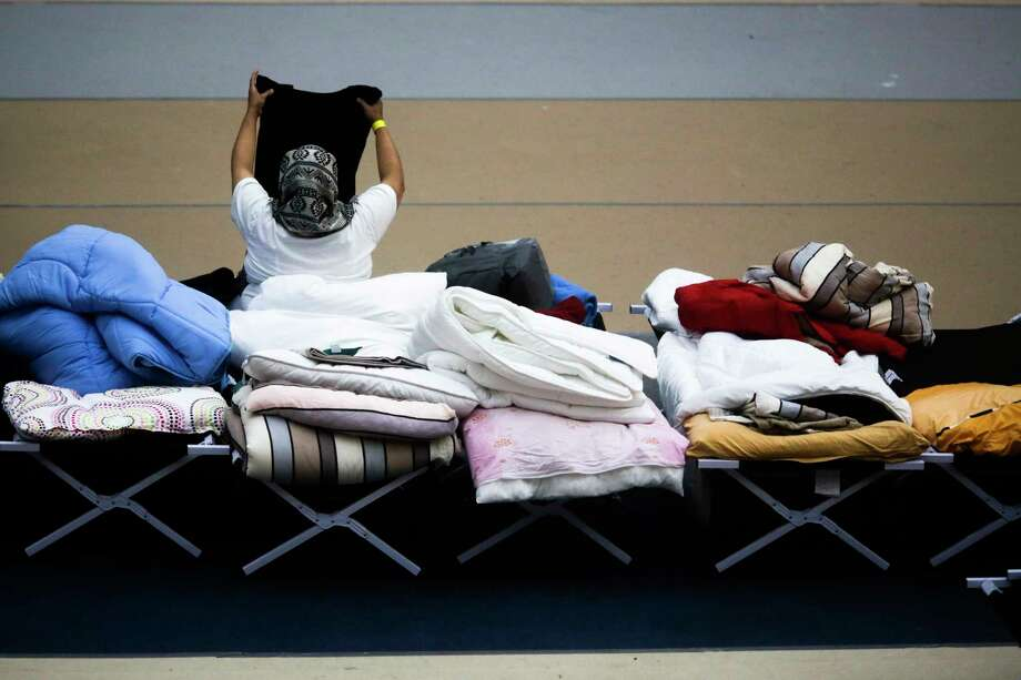 A migrant woman sits on a camp bed and checks her belongings at an emergency refugee shelter at a sports hall in Berlin, Friday, Oct. 23, 2015. Up to 1000 people can be housed in two sports halls of this shelter for their first days in Germany, before they get officially registered and distributed to other accommodations. Photo: AP Photo/Markus Schreiber    / AP