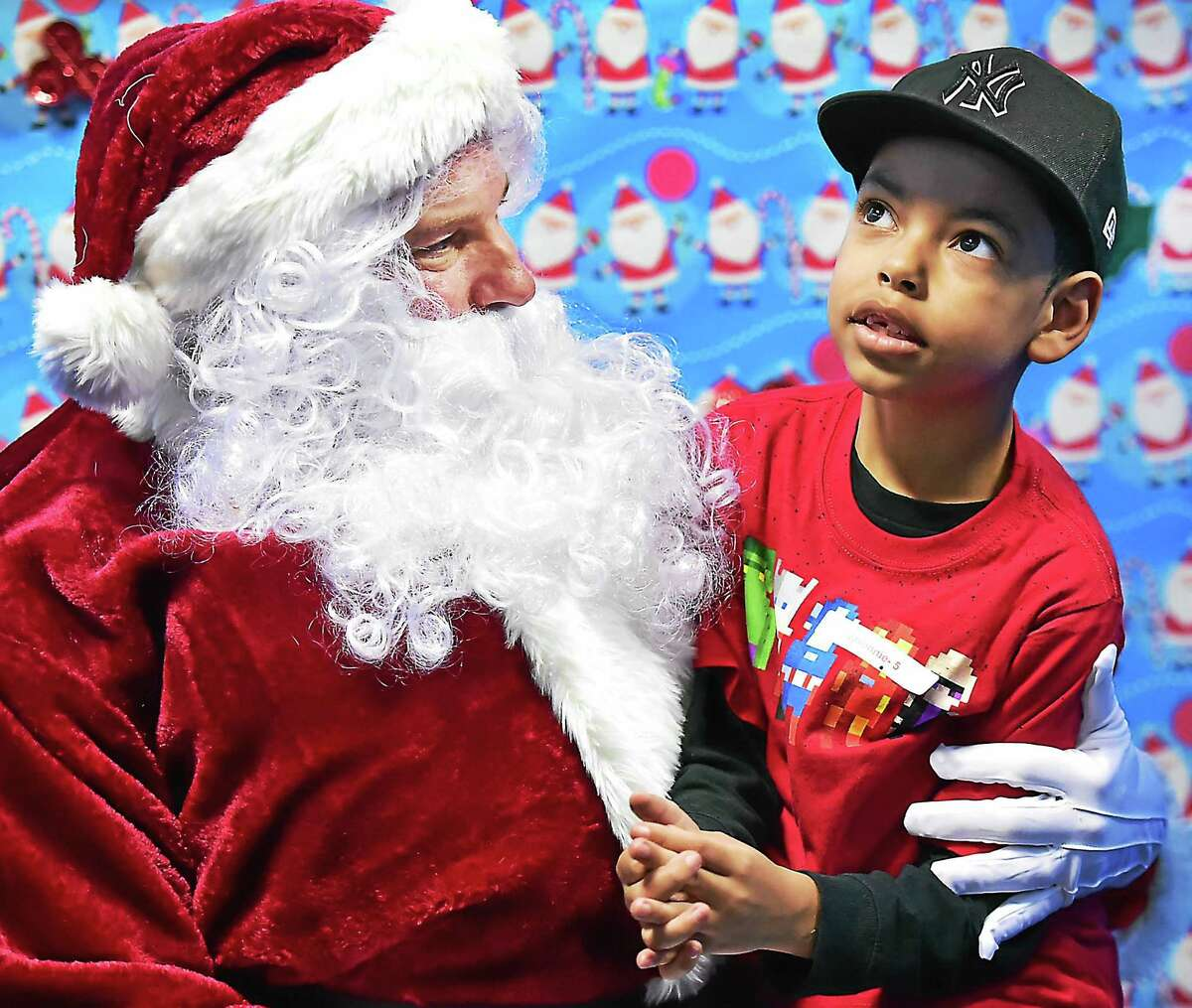 """(Catherine Avalone - New Haven Register) Javonnie Rodriguez, 7, of West Haven sits on the lap of a """"sensitive"""" Santa who meets with children on the autisim spectrum one on one in a low-stimuli setting at a holiday party, Saturday, December 19, 2015, at ASD Fitness at 307 Racebrook Road in Orange."""