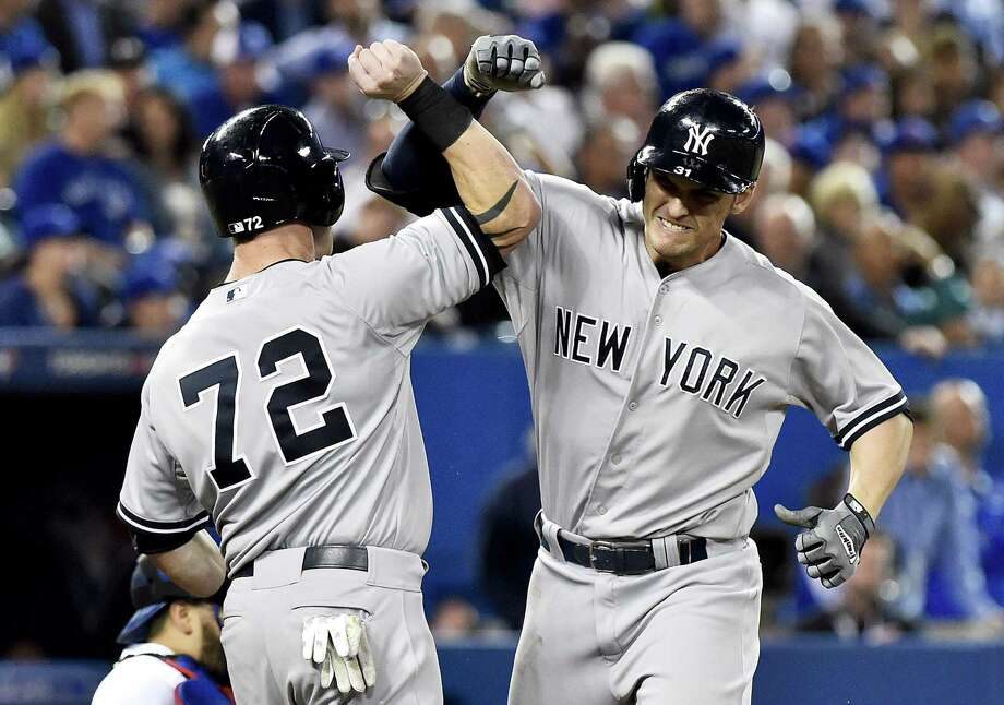 The New York Yankees' Greg Bird, right, celebrates a three-run home run with teammate Slade Heathcott during the tenth inning of Tuesday's win over the Blue Jays in Toronto. Photo: Nathan Denette — The Canadian Press   / The Canadian Press