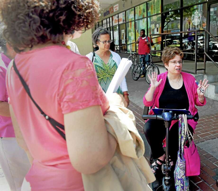 Attorney Melissa Marshall of West Hartford, center, coordinator of the Connecticut Cross Disability Lifespan Alliance who is a consultant on Americans with Disabilities Act training, conducts a tour of downtown New Haven business sites on Chapel Street Thursday, July 23, 2015 as part of the celebration of the 25th anniversary of the ADA. Photo: Peter Hvizdak — New Haven Register   / ©2015 Peter Hvizdak