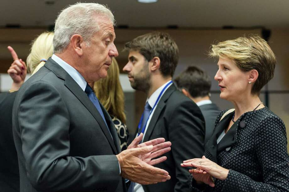 European Commissioner for Migration and Home Affairs Dimitris Avramopoulos, left, talks with Swiss Justice Minister Simonetta Sommaruga at the start of a meeting of EU justice and interior ministers at the EU Council building in Brussels on Tuesday, Sept. 22, 2015. EU interior ministers aim to agree on a plan to share 120,000 refugees in countries worst hit by the influx among their other EU partners. Photo: AP Photo/Geert Vanden Wijngaert    / AP