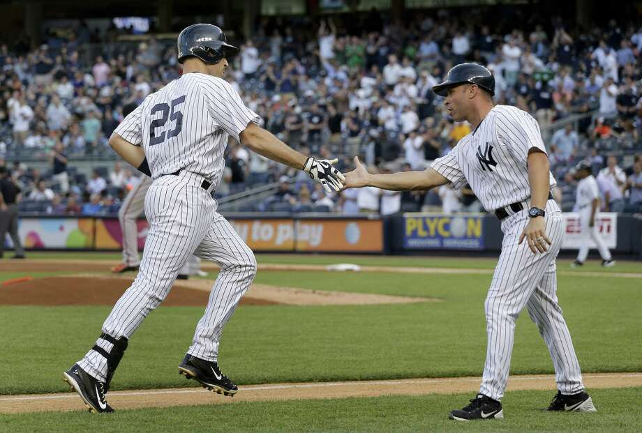 The Yankees' Mark Teixeira (25) is greeted by third base coach Joe Espada as he rounds the bases after hitting a two-run home run against the Baltimore Orioles. Photo: Julie Jacobson  — The Associated Press   / AP