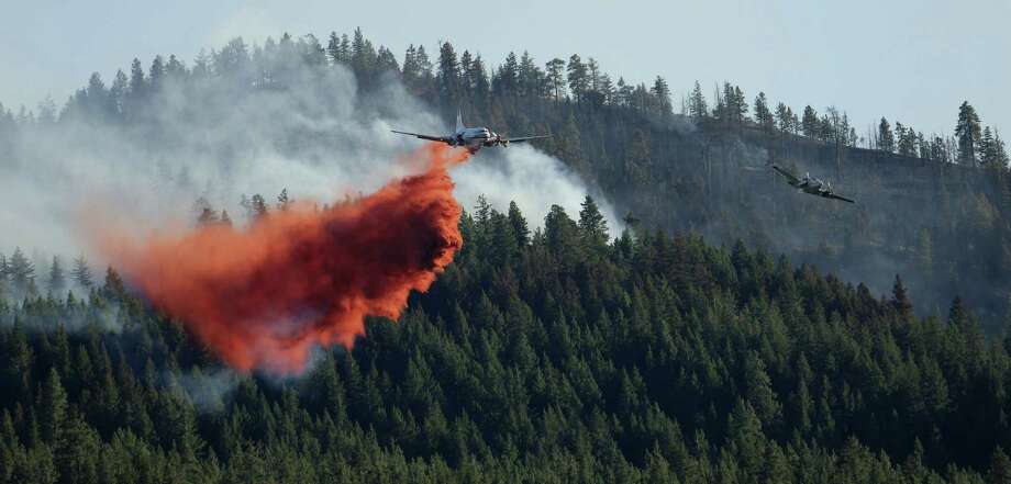 Guided by a spotter plane at right, an airplane drops fire retardant while fighting a wildfire near Twisp, Wash., Aug. 21. Photo: AP Photo   / AP