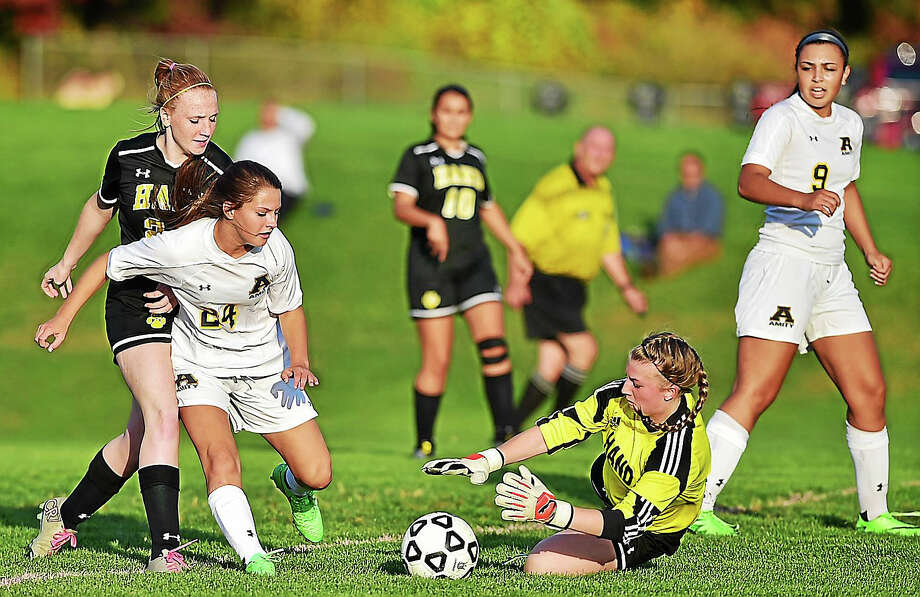 Hand goalie Amy Boswell defends the Tigers' goal as Amity's Kaylee Huber takes a shot on Wednesday, October 21, 2015, at Amity in Woodbridge. The Amity Spartans defeated the Daniel Hand Tigers, 4-0. Photo: Catherine Avalone -- New Haven Register   / Catherine Avalone/New Haven Register