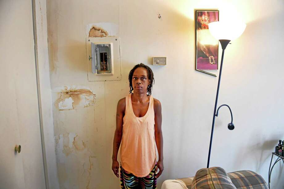 Diane Turner stands by the electrical box — surrounded by areas of water leaks in the wall — in  her Church Street South apartment . Photo: Peter Hvizdak — New Haven Register   / ©2015 Peter Hvizdak