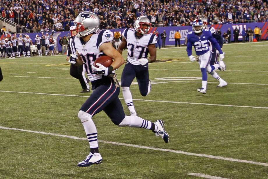 New England Patriots receiver Danny Amendola runs away from New York Giants defensive back Tramain Jacobs during Sunday's game in East Rutherford, N.J. Photo: Gary Hershorn — The Associated Press   / FR171392 AP