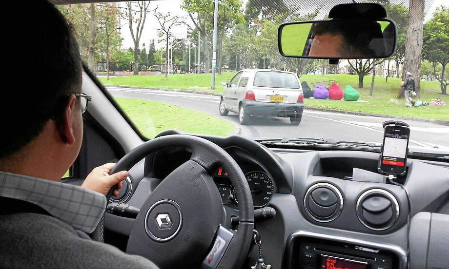 A driver gives a ride while running the Uber app on a smartphone. The company recently announced it is lowering rates in Connecticut. Photo: File Photo