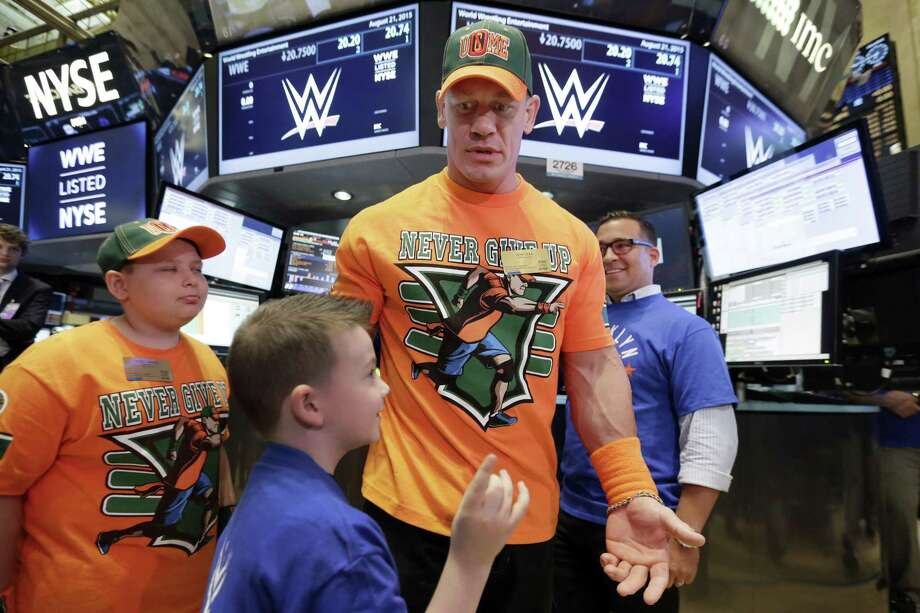 World Wrestling Entertainment Superstar John Cena, center, is accompanied by Make-A-Wish participants Rocco Lanzer, left, and and Evan Maher, as he visits the trading floor before ringing the New York Stock Exchange opening bell, on Friday. Photo: Richard Drew — The Associated Press   / AP