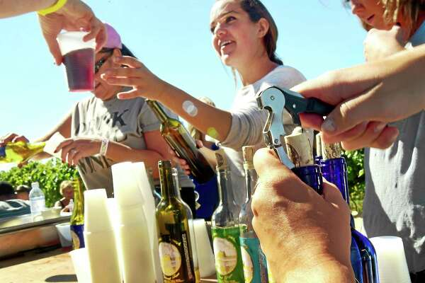 (Peter Hvizdak - New Haven Register)  Wine is served to volunteers grape pickers at Gouveia  Vineyards in Wallingford Sunday during the vineyard's annual wine grape harvest. Approximately 310 people from Connecticut, Rhode Island, Massachusetts, New York, New Jersey and Chicago participated as volunteer pickers harvesting 75 percent of the grapes on 25 acres of land, collecting 6 different varietals that amount to 60 tons of grapes before the crushing process. In return, the volunteers were treated to a food buffet, wine and traditional Portuguese dancing.