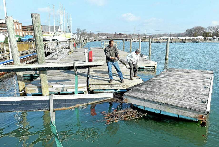 Branford Marina owner Chris Anderson (left) and Fausto Zhicay position a section of floating dock for winter removal. Photo: Arnold Gold — New Haven Register